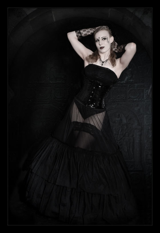 Beautiful model wearing black corsage and a transparent black skirt posing in front of an old black gate - © by Magistus