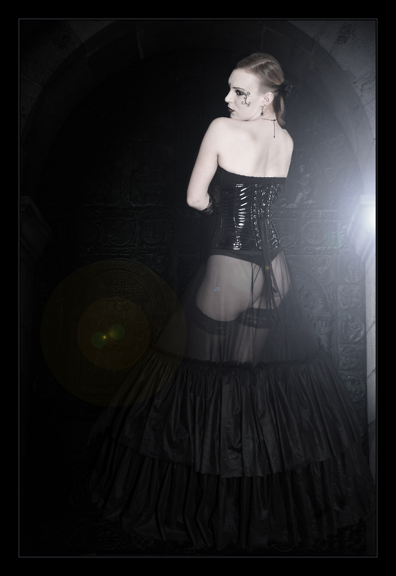 Gothic Beauty - Sexy Photo of a gothic style model with black corsage and a transparent skirt showing her bum posing in front of a black gate - Photo © by Magistus