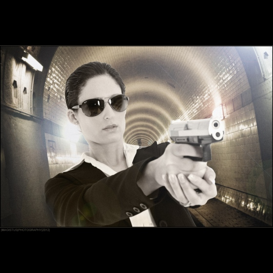 Detective - Agent-Composing with cool and beautiful model wearing sunglasses holding gun in her hands standing in a long tunnel - Photo © by Magistus