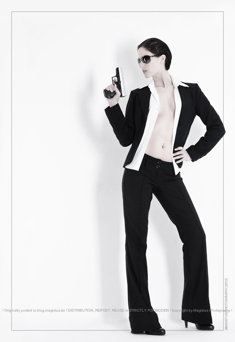 Fashion Agent - Sexy Fashion with beautiful model wearing black business suite barely covering her chest and breats posing as agent with a gun -- Photo © by Magistus
