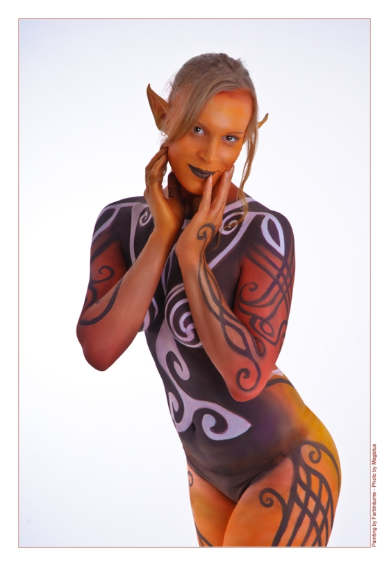 Celtic Colors - Model with a full bodypainting in colorful style with celtic signs posing with elfen ears - Photo © by Magistus