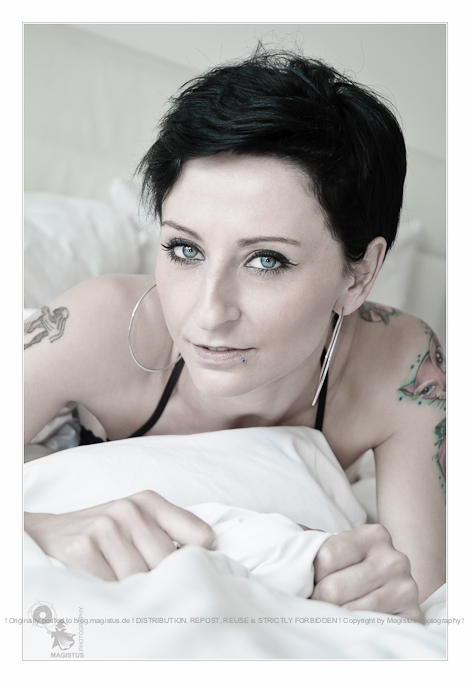 White Bed - Lingerie Close-up Portrait with beautiful blue eye model posing on the bed showing her beautiful tattoos- © by Magistus