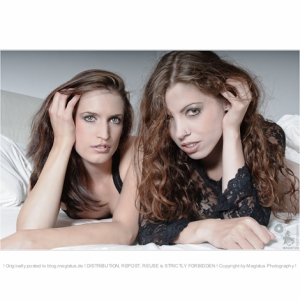 Two Beauties - Girl/Girl Close-up Portrait with two beautiful models with long hair posing on the bed looking in the camera - © by Magistus