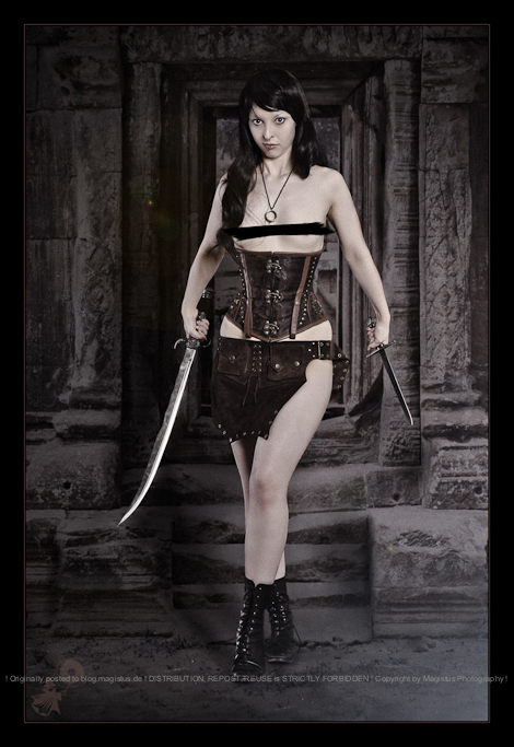 Temple Fighter - Erotic Figthergirl Shooting with topless and beautiful warrrior model wearing leather corsage and two blades posing half naked in front of an ancient temple - CENSORED © by Magistus