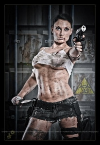 Fighting Beatuy - Erotic Fightergirl Shooting with hot and sexy model covered in oil and dirt posing tough with a gun and a dagger wearing tight jeans hotpants and a very small tanktop covering barely her big boobs - © by Magistus