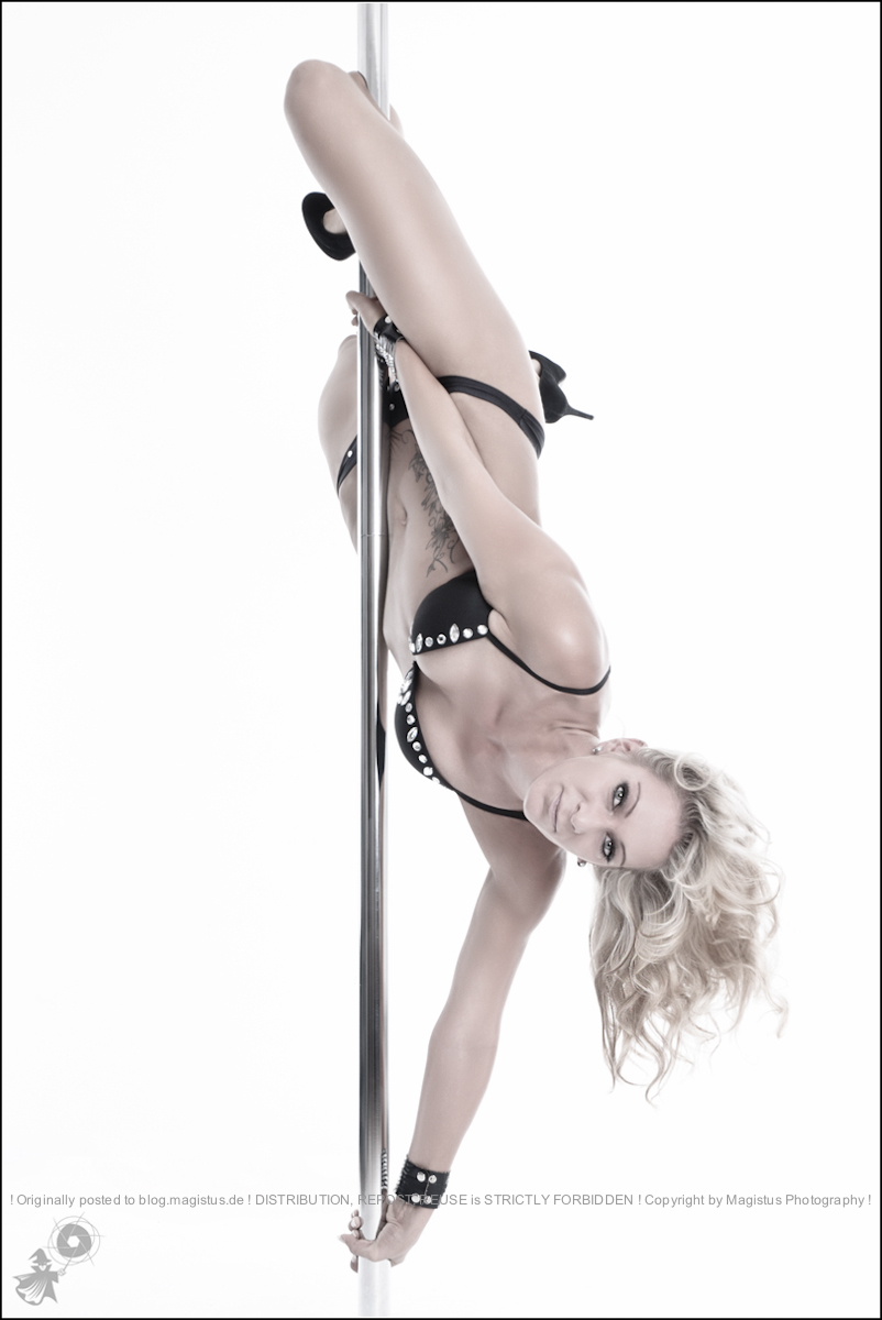 Poledance - Acrobatic and Sexy Photoshooting with hot blonde model in an athletic pose on the pole halfe naked wearing only black lingerie.- © by Magistus