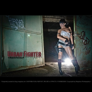 Urban Fighter - Erotic Action OnLocation Photoshooting with sexy model posing with a gun and dagger topless in a dark location wearing tight and short jeans hotpants and a dirty tanktop showing one of her beautiful boobs with a piercing. - © by Magistus