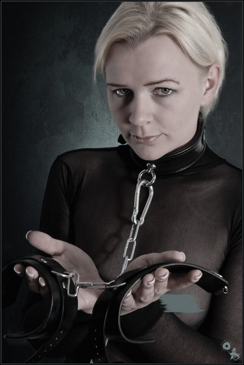 Submissive - Fetish Close-up Portait with blond submissive slave girl with a nakelace and a chain presenting her hand cuffs. - © by Magistus