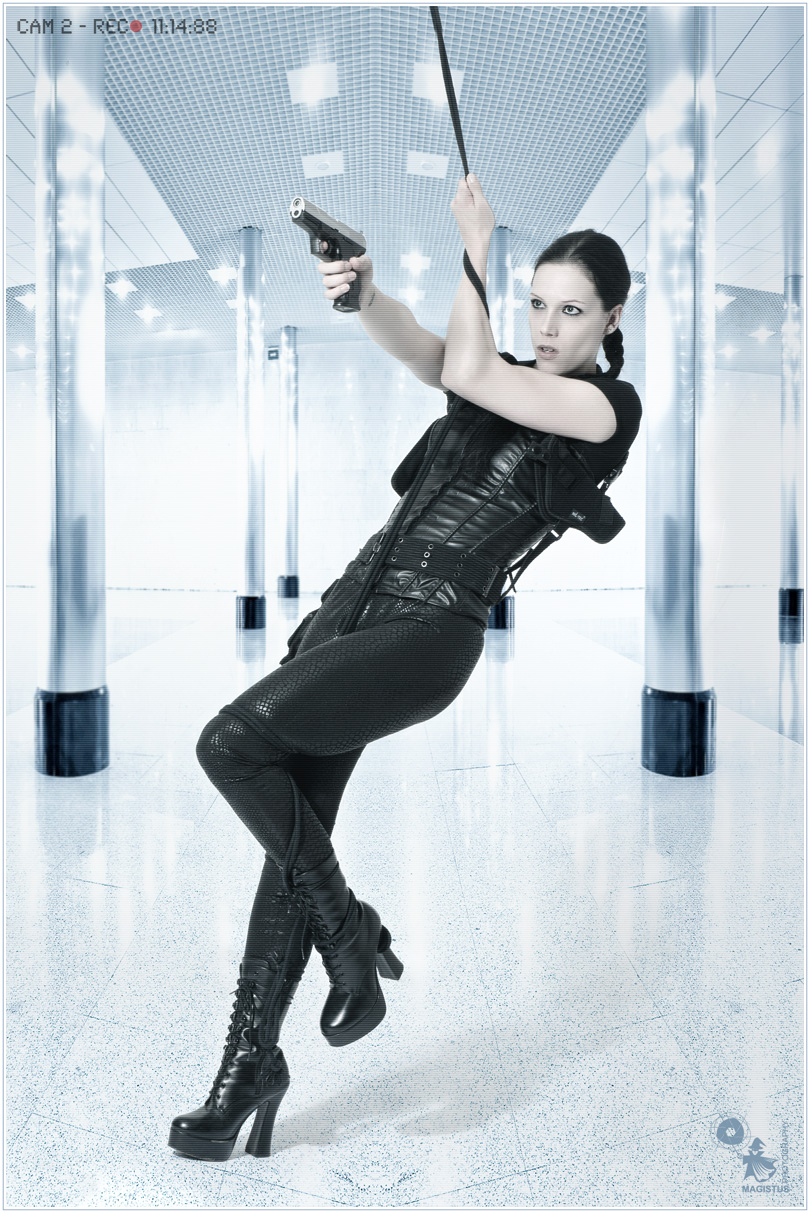 Future Hunter - Fightergirl Composing with a beautiful, tough and sporty model wearing black leggins and a black corsage holding a gun in her hands. - Artwork © by Magistus - Backround © Vladitto - Fotolia.com