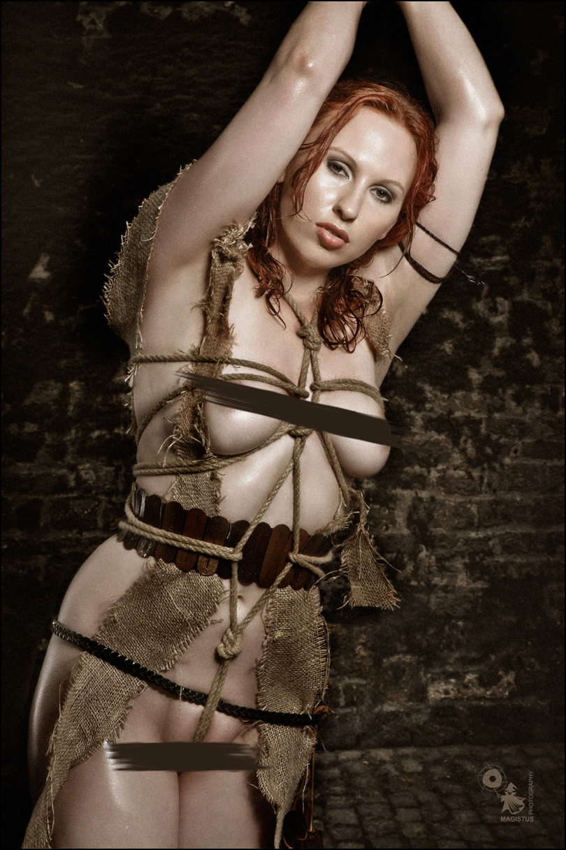 Bound Slave - Fetish and Erotic Art with a busty naked girl bound in a dark place showing her big naked breasts and a rope tight around her body. - © by Magistus