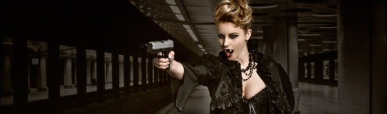 Fighting Vampire - Fantasy Vampire Composing with a great vampire girl in black gothic dress pointing angry with a gun in the underground showing a big cleavage and her fangs. - © by Magistus