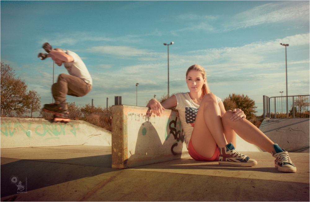 Summer n Skates - Outdoor Portrait Shooting on Skater Ground with fantastic blonde model in hotpants and a jumping skater in the Background. - © by Magistus