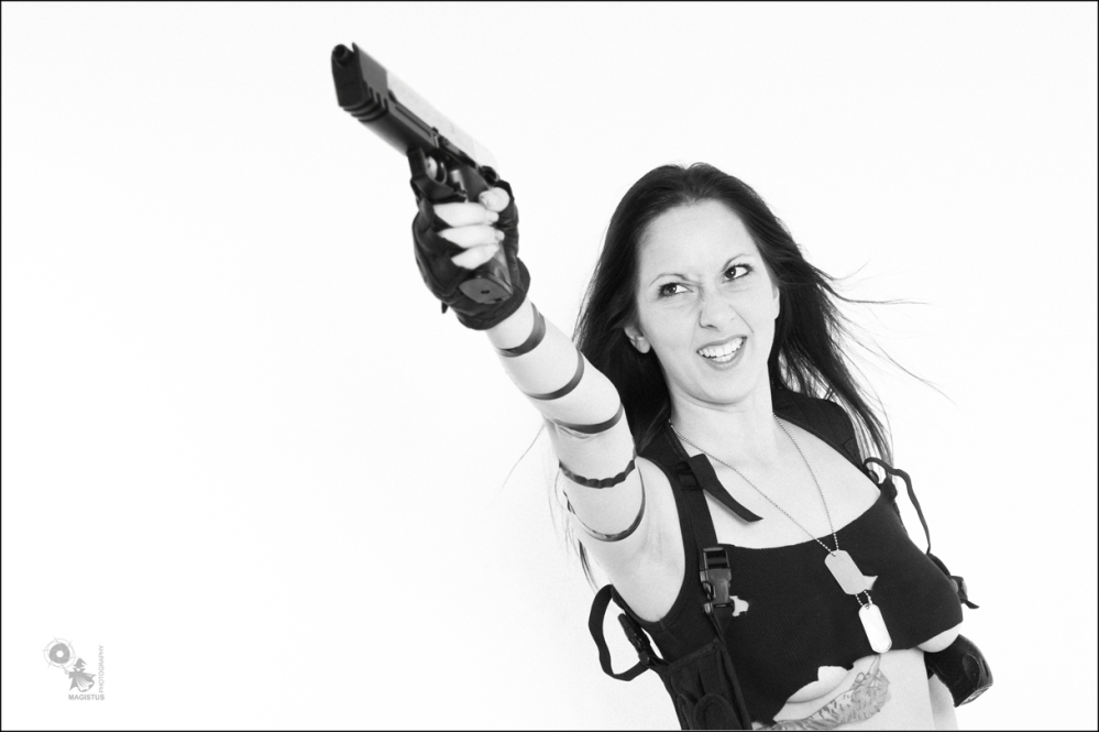 Action Shooter - Sexy Fightergirl Black & White Photo with a busty girl in a very small top posing with a big gun showing a litte bit auf her big boobs. - © by Magistus