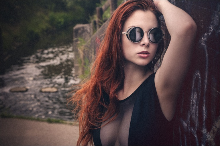 Sun Glasses - super sexy and beautiful closeup portrait auf a redhead beauty with nice cleavage - © by Magistus