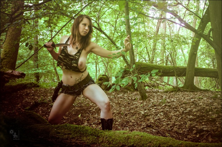 Dschungle Fighter - Hot and Erotic Busty Fightergirl posing half naked with a dager in the woods wearing sexy jeans hotpants showing one big naked breast - © by Magistus