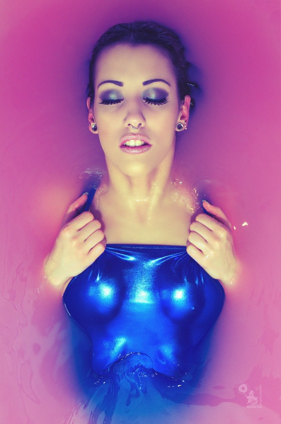 Blue in Pink - Hot pierced model is posing in pink water wearing a blue swimsuite showing her cleavage - © by Magistus