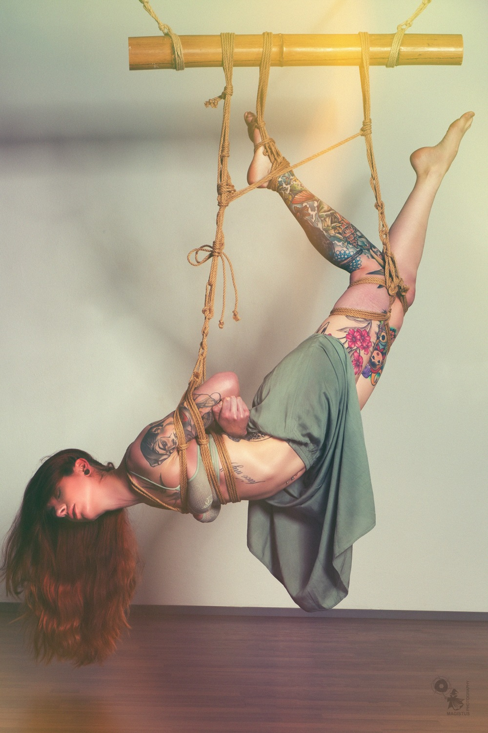 Flying - fantastic shibari photo with great tattooed model hanging in tight bondage wearing lingerie - © by Magistus - ropework by Hr. Pieps