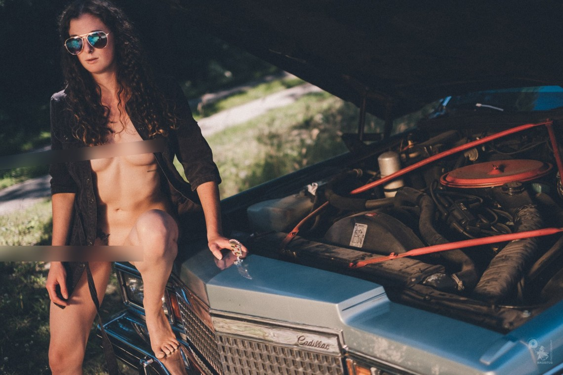 Super sexy girl with curly hair is posing topless in front of a cadillac